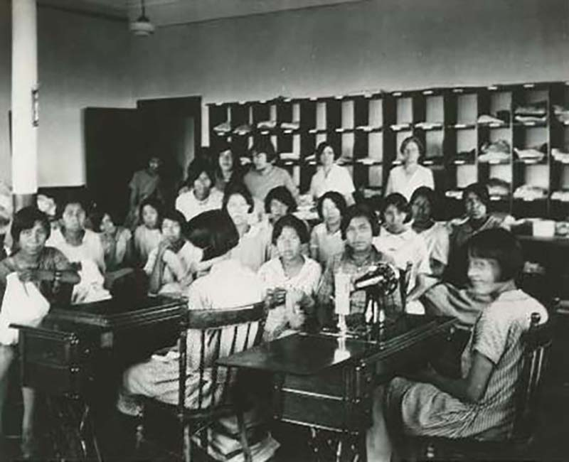group of people at sewing machines at Edmonton Poundmaker school