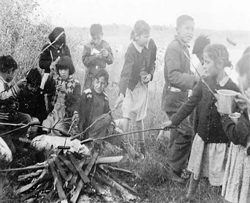 Group of children roasting hotdogs on fire at Gordon's school