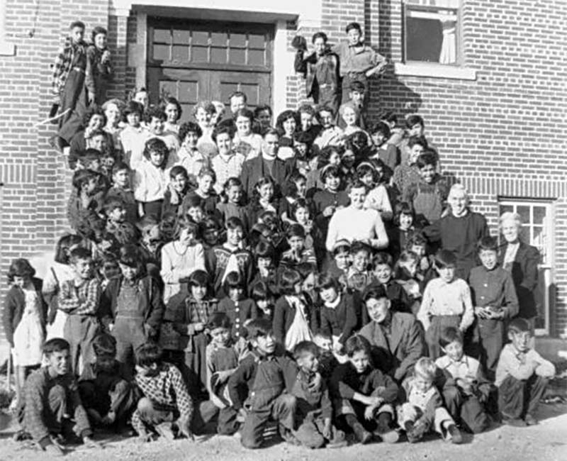 Group of students and teachers outside building at Gordon's school