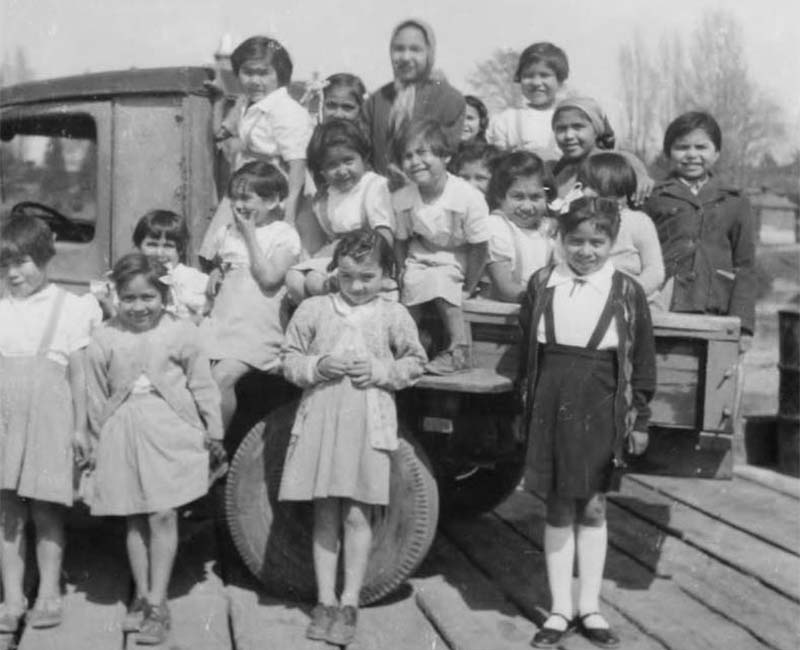 Group of students sitting and standing by truck from Kupersland School