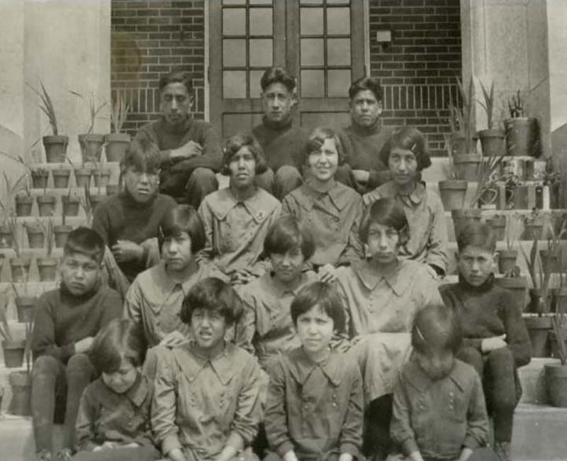 Group of students sitting on steps of building at Muscowequan Touchwood School