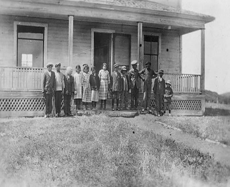 Group of people outside building at Sacreee St. Barnabas school