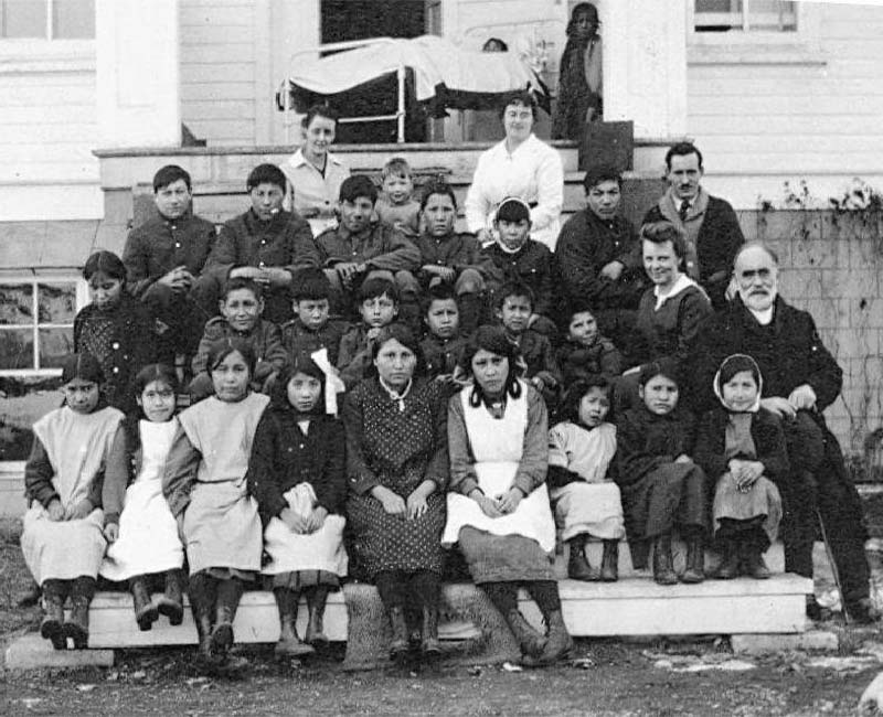 Group of people sitting in front of Sarcee St. Barnabas school