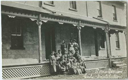 group of people sitting and standing in front of building
