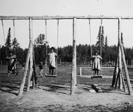 Group of children playing on swing set.