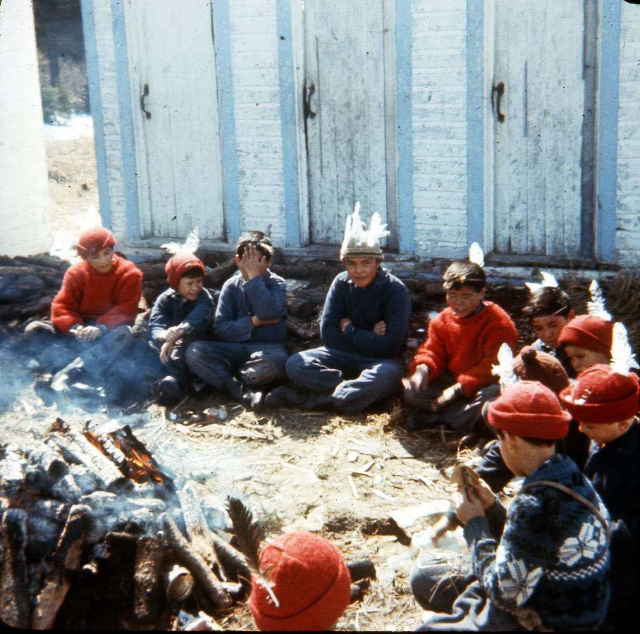 Group of children sitting around a fire