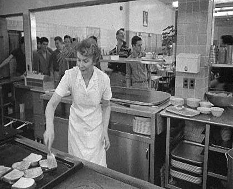 Person cooking in kitchen at Akaitco Hall while students line up