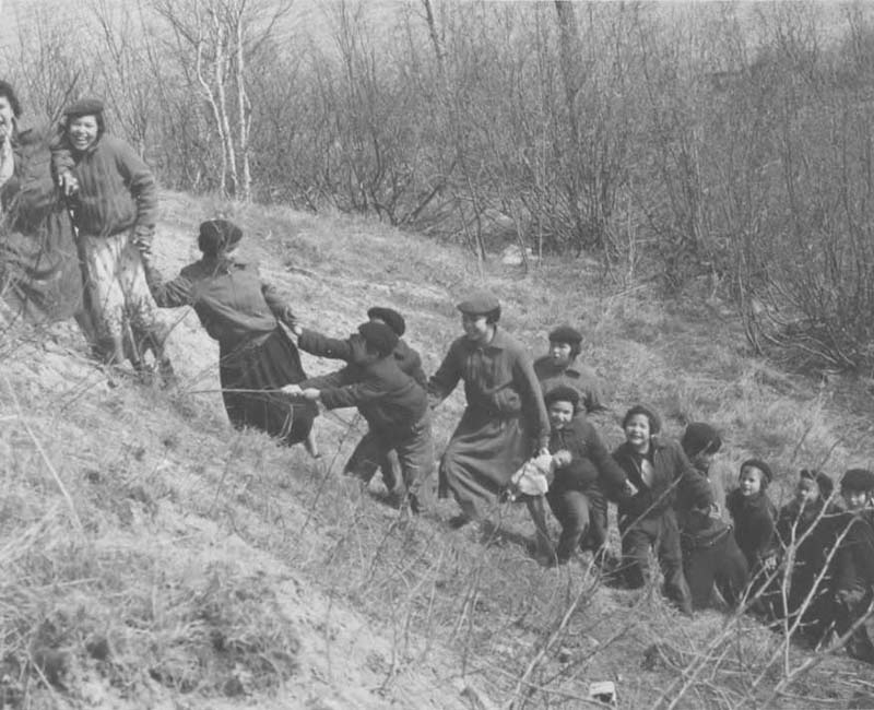 Group of people climbing hill at Amos school