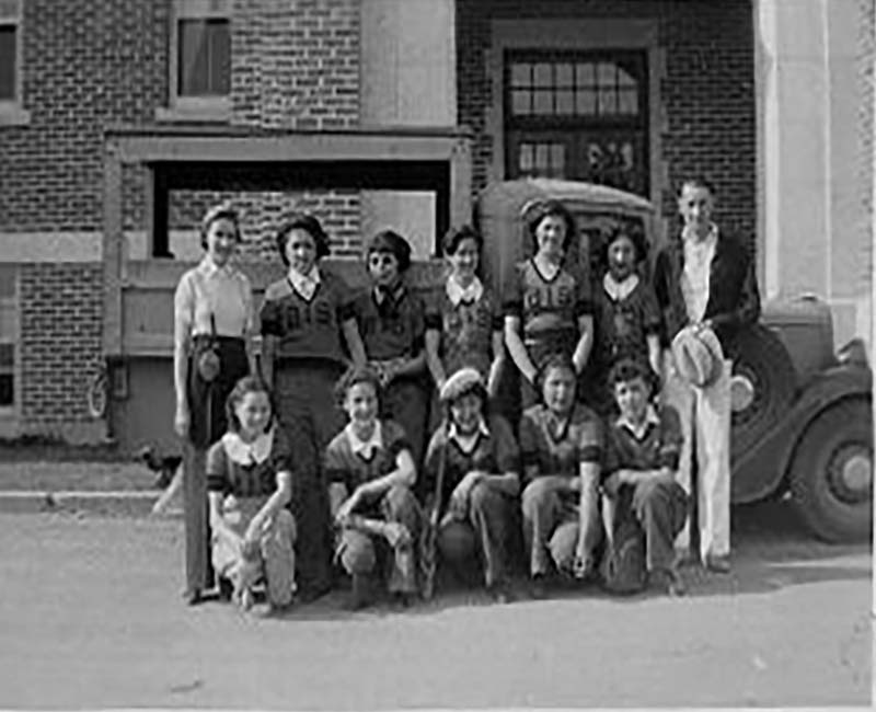 Group of students in front of car in front of Brandon school building