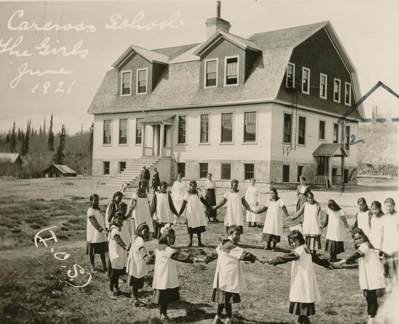 Group of students standing in circle holding hands outside Carcross Chooutla school