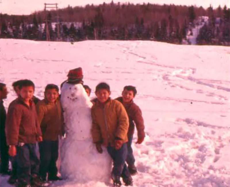 Children from Cecilia Jeffrey school outside building a snowman