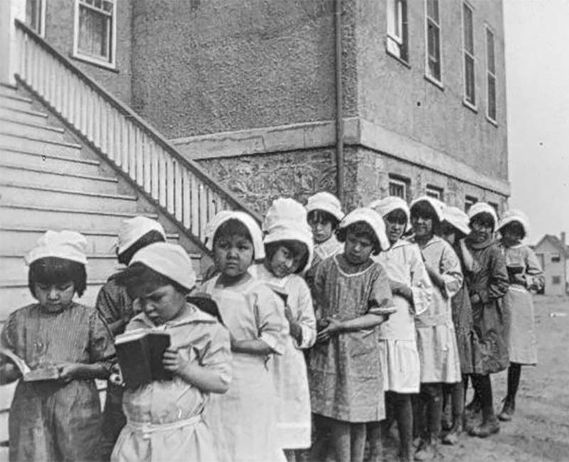 Children standing with books outside of Chapleau St. John's school