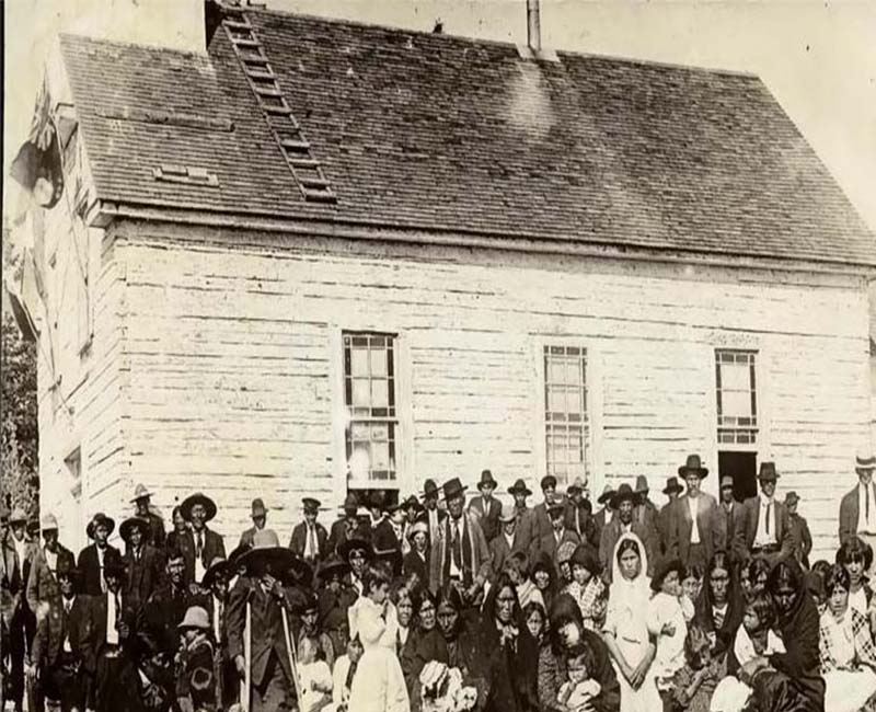 Group of people standing and sitting in front of Cross Lake school building