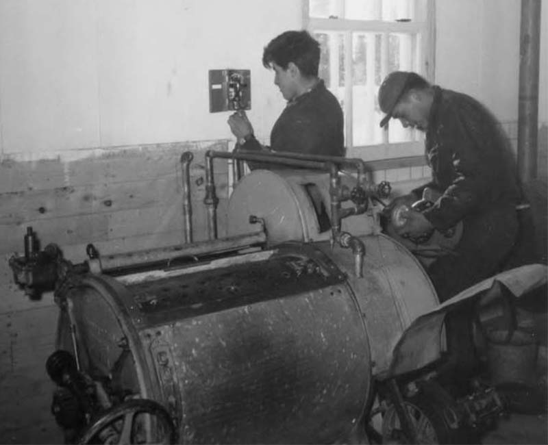 Two people fixing machine at Fort George Roman Catholic school
