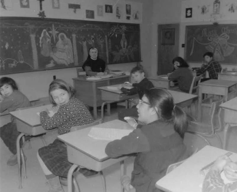 Students in desks at Fort George Roman Catholic school