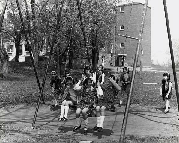 Children playing on swings by building at Mohawk Institute