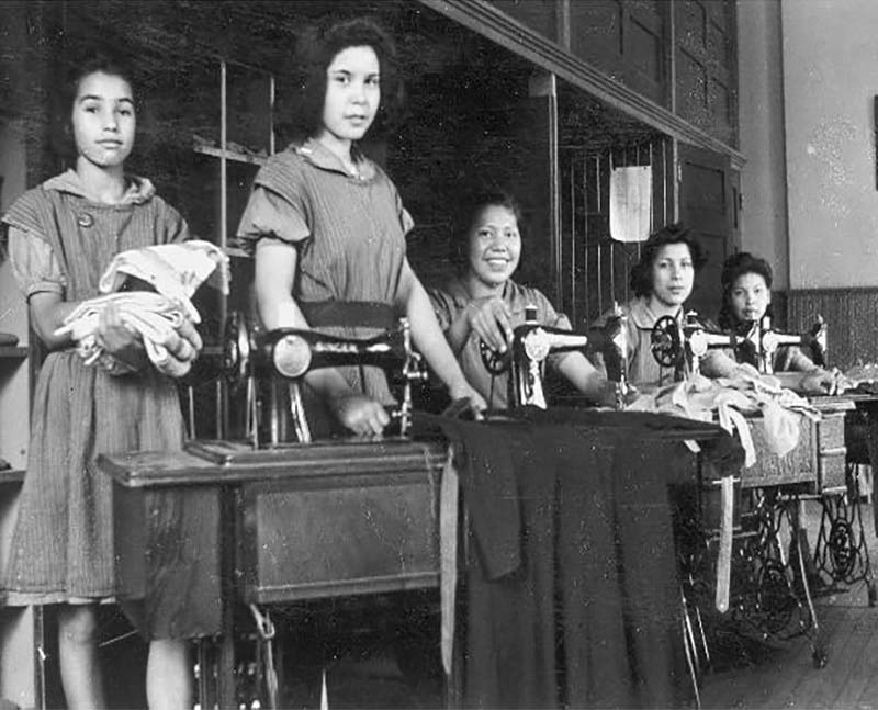 Group of people sewing on machines in Mohawk Institute school