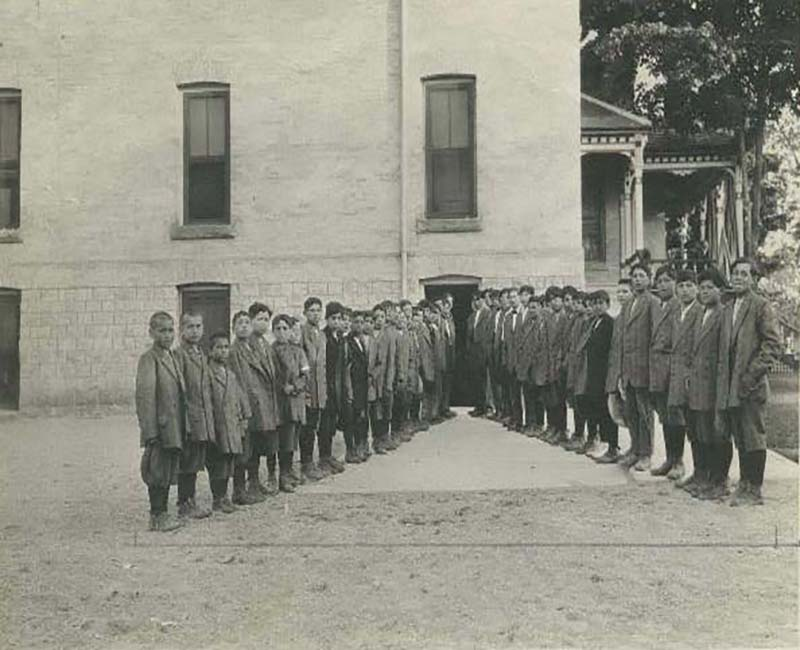 Group of people posing for photo outside of a Mount Elgin school building