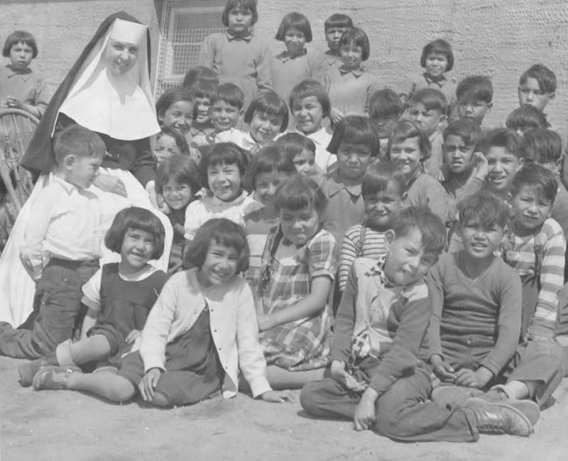 Group of students and nun posing for photo in front of Sept-Iles school