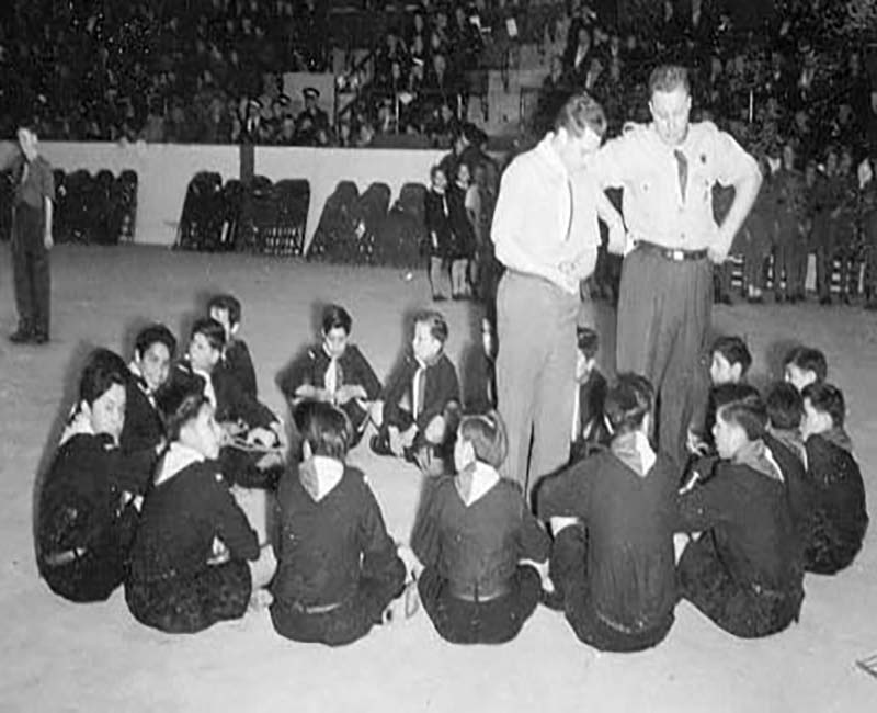 Group of children sitting on floor in a circle in Shingwauk school