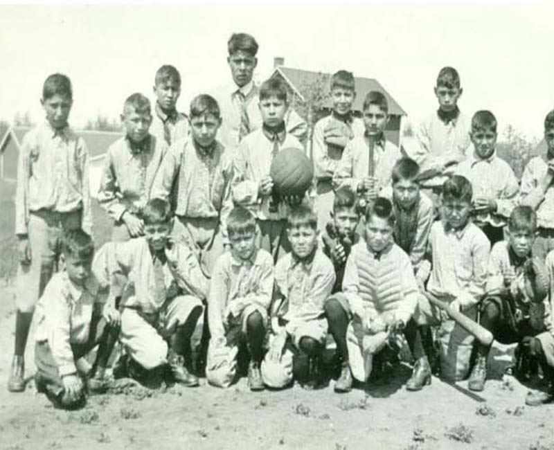 Group of students playing baseball outside St. Phillips school