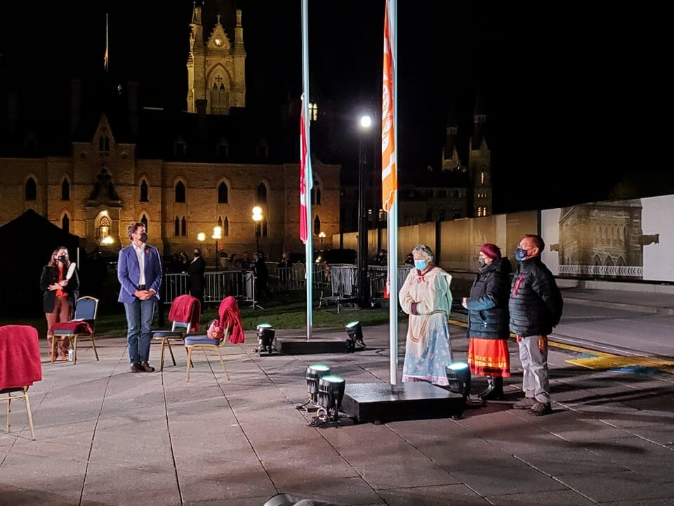Survivors stand during Algonquin honour song